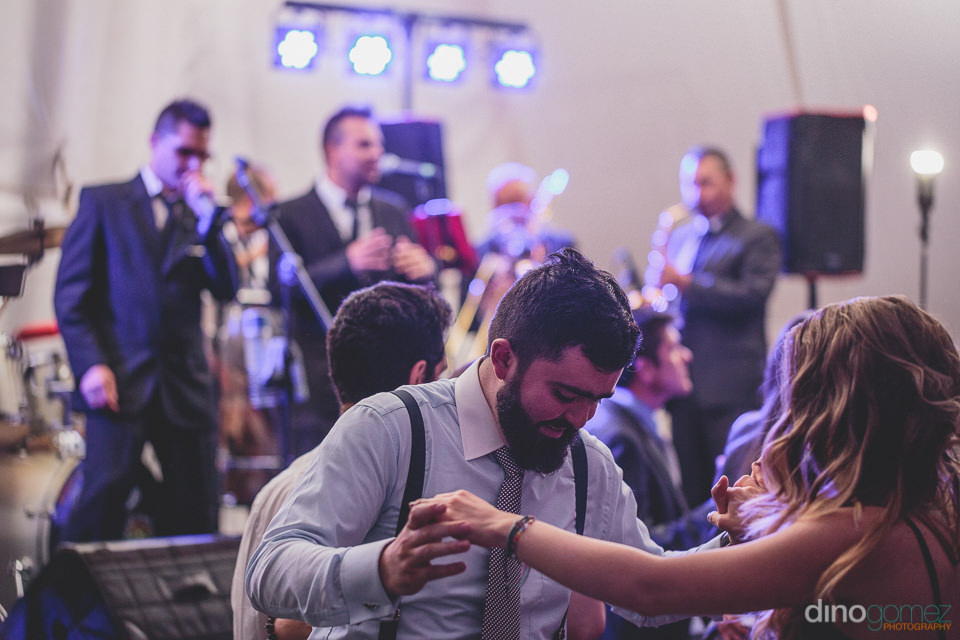 friends and family of the bride and groom dance to live music