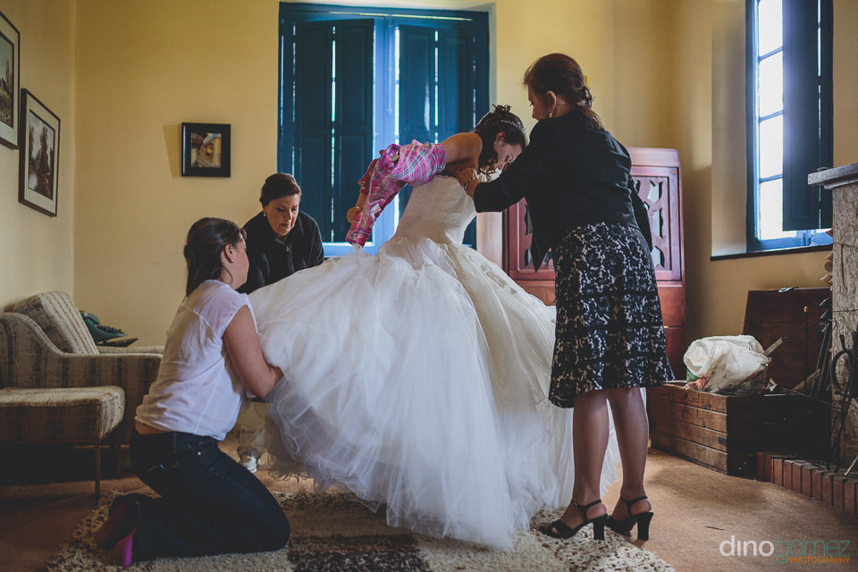 the bride puts on her wedding dress with the help of some family