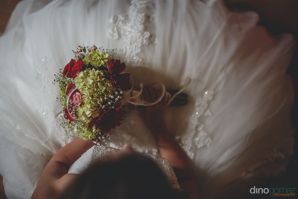 overhead photo of bride holding bouquet in her lap