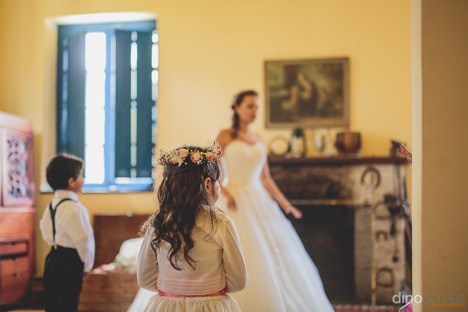bride in wedding dress with children looking on