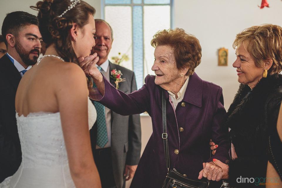 family congratulate the bride at bbq backyard wedding photograph
