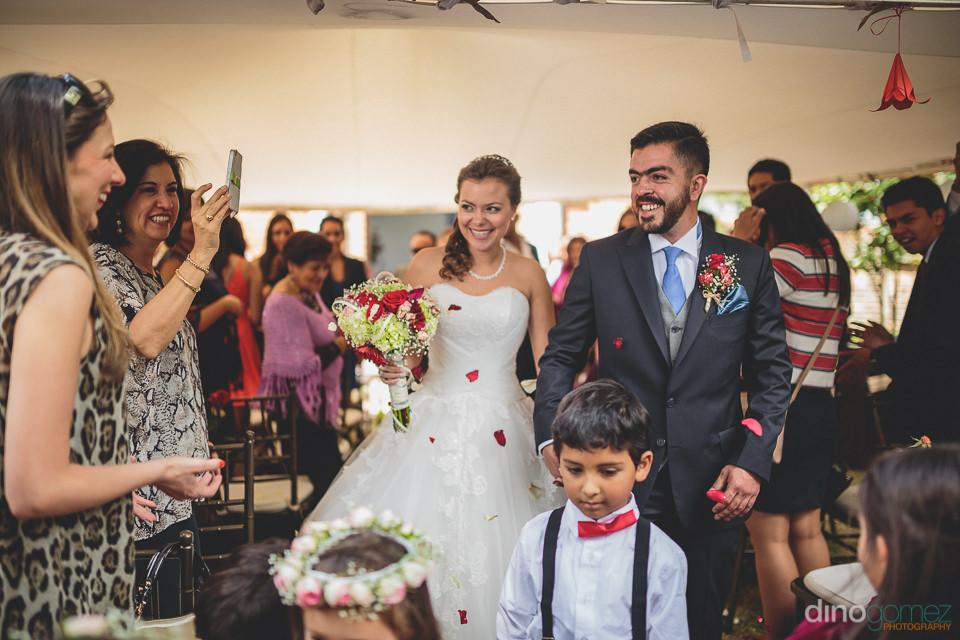 newlyweds walk hand in hand at flora farm wedding