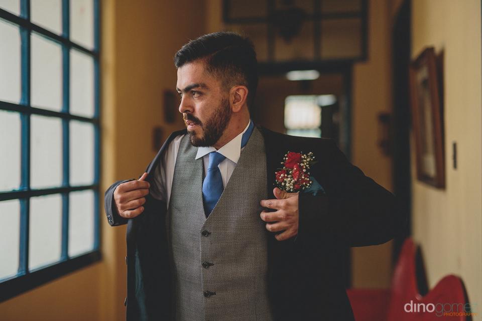 groom walks through hacienda on wedding day