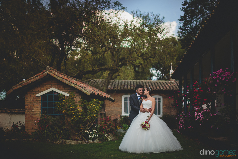 happy wedding couple standing in courtyard of countryside villa