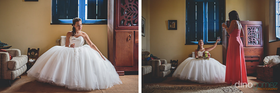 bride relaxes with bridesmaid on wedding day photo by dino gomez