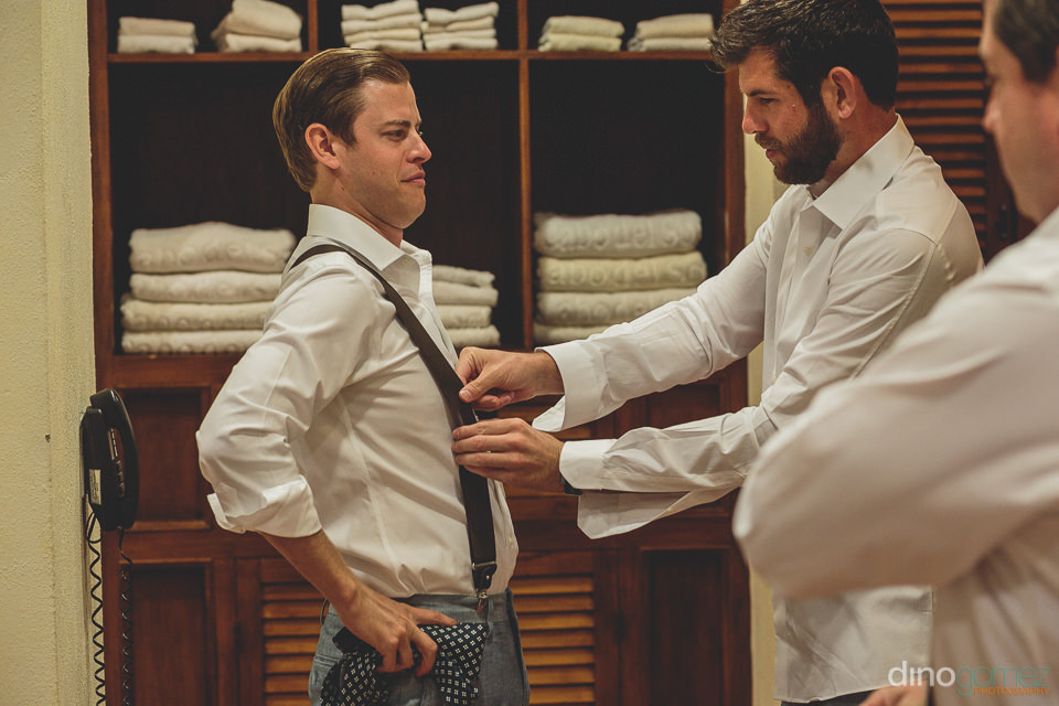groomsmen help groom with suspenders