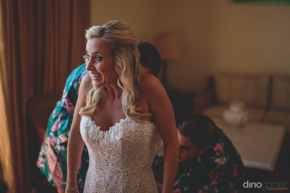 smiling bride puts on wedding dress with help from bridesmaids