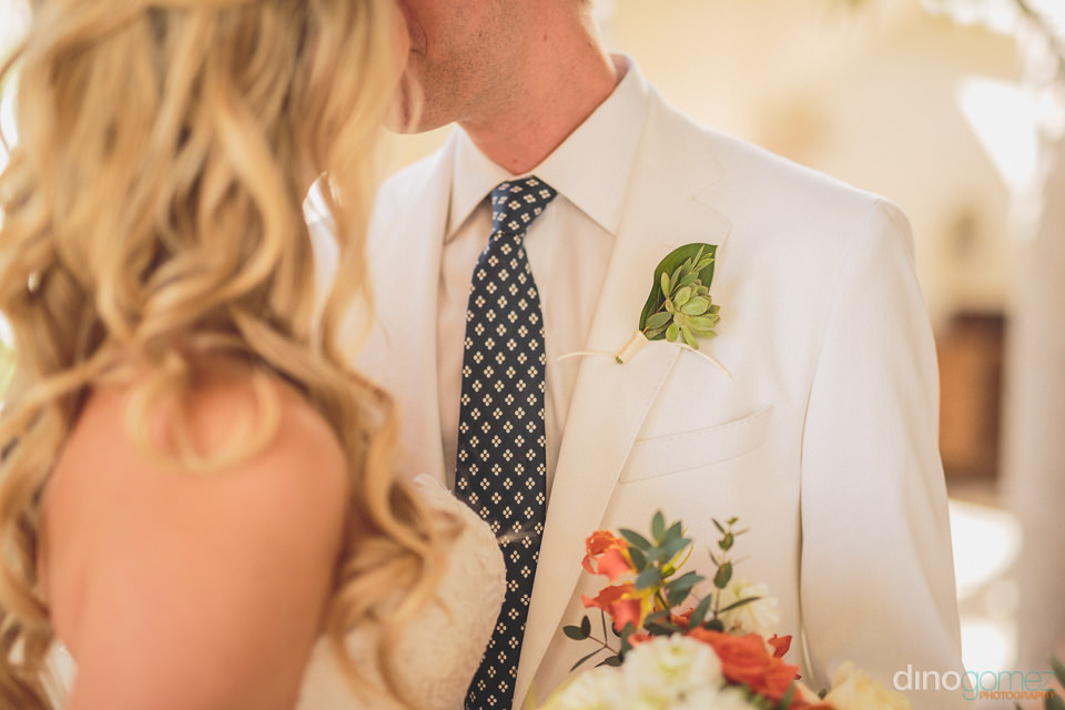groom wearing a white suit with green boutonniere