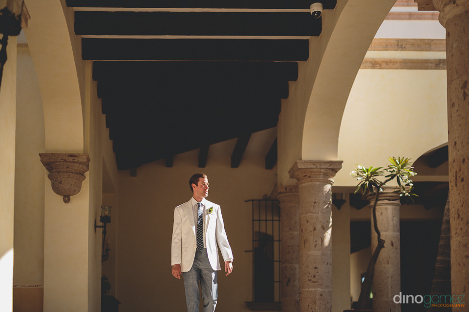 groom walks towards beachside wedding in cabo