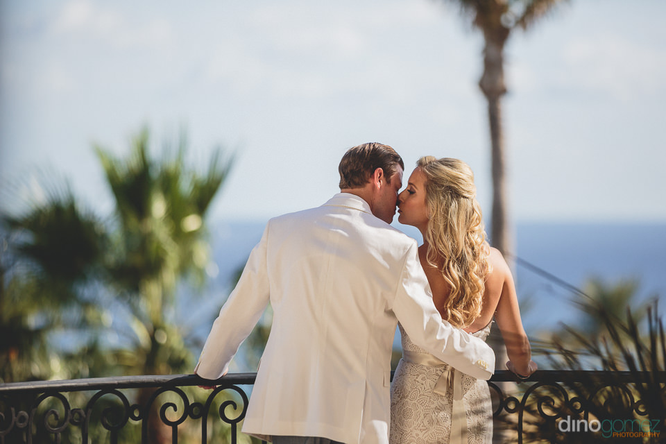 newlyweds on balcony at cabo del sol overlooking the ocean
