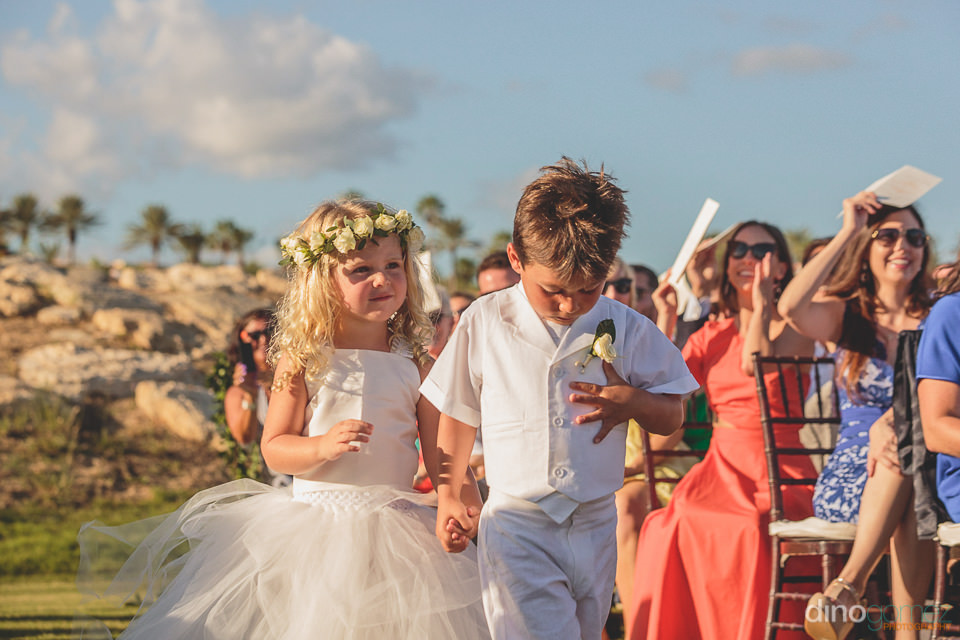 children dressed like bride and groom walk down the aisle