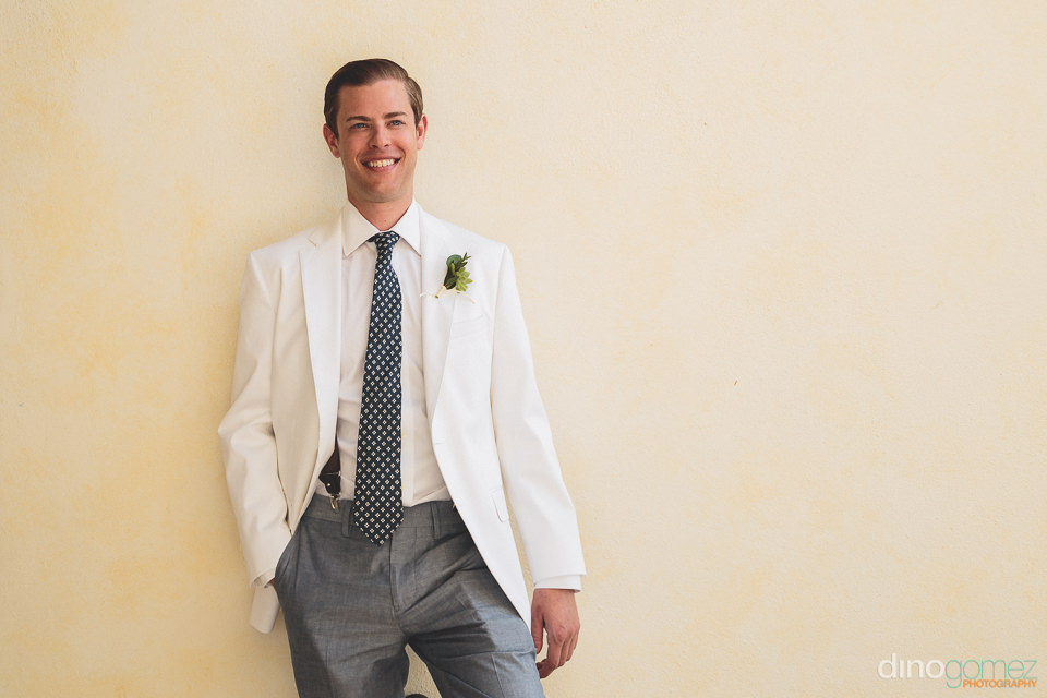 groom wears white wedding suit jacket