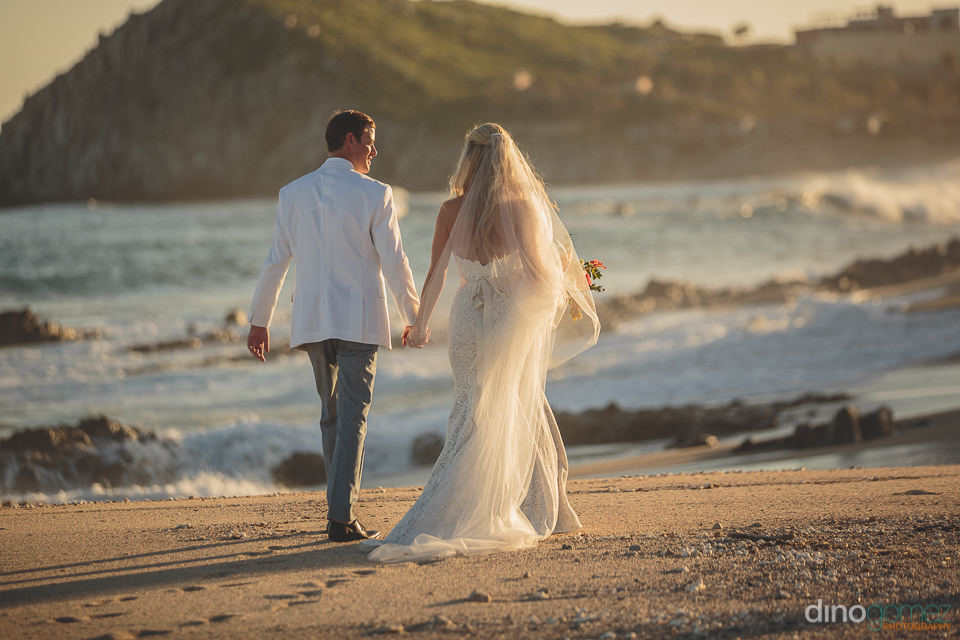 newlyweds walk along the beach in los cabos photo by dino gomez
