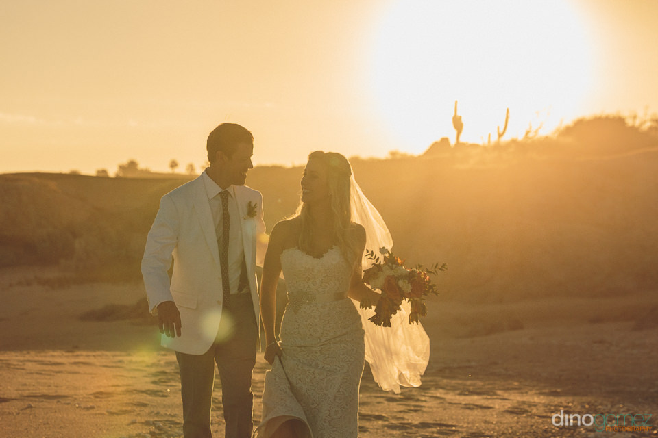 sunset wedding photo by dino gomez of bride and groom