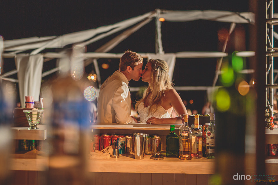 newlyweds kissing alone at the bar