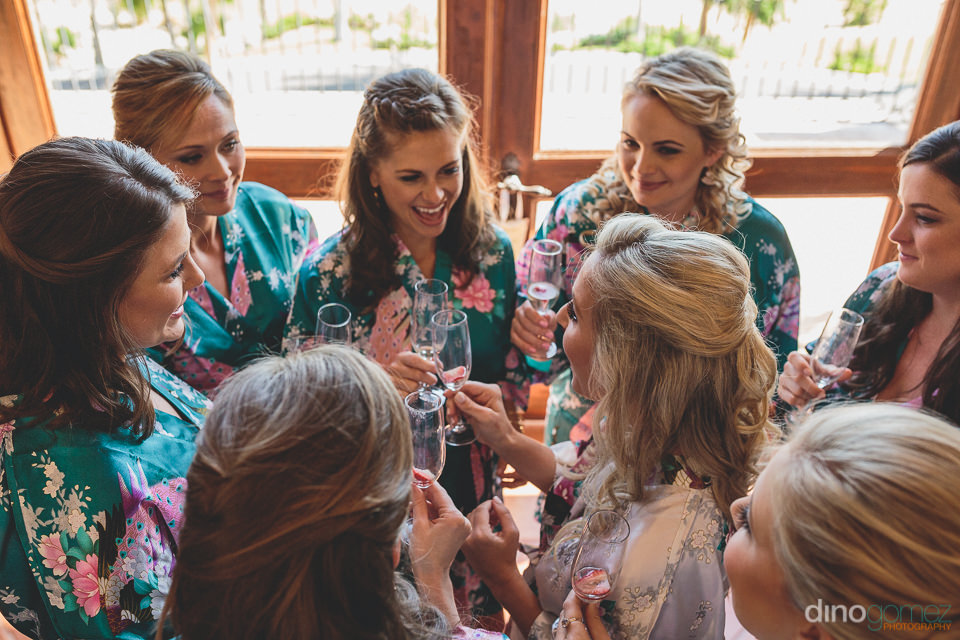 bridesmaids and bride drink champagne before cabo wedding