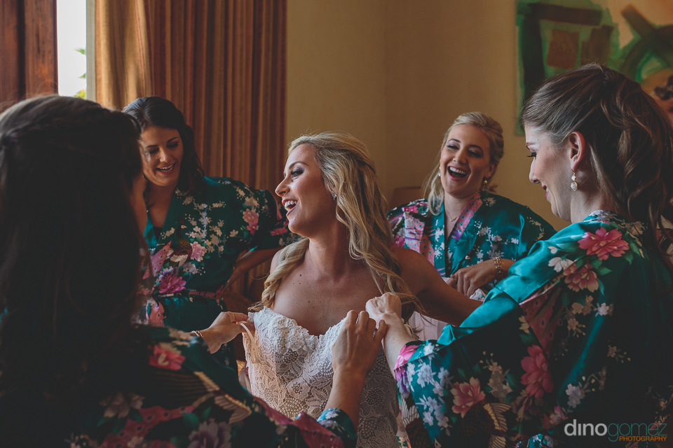 bridesmaids help the bride into her wedding dress