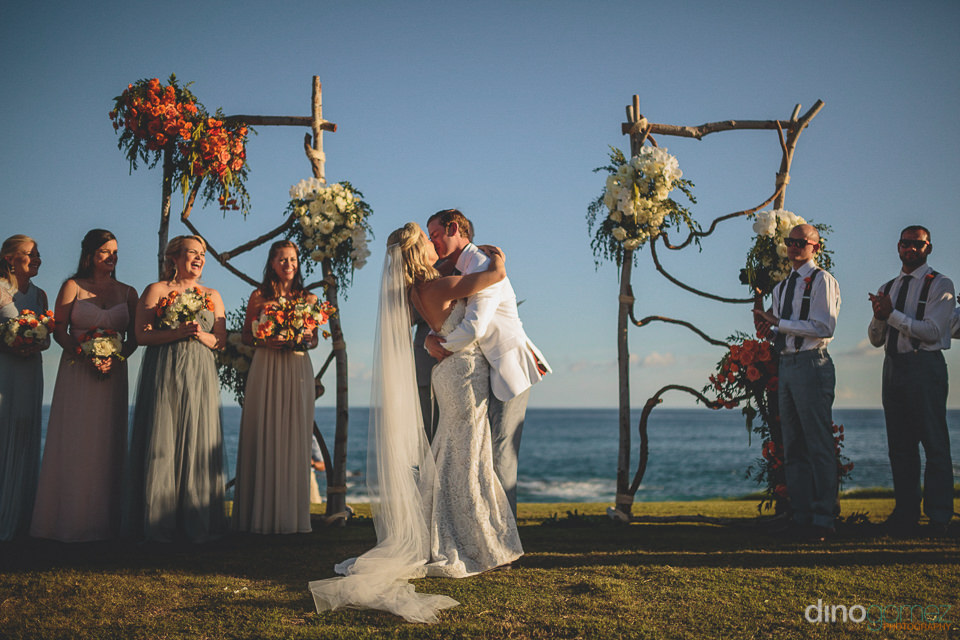 newlyweds kiss at beachside cabo wedding at cabo del sol resort