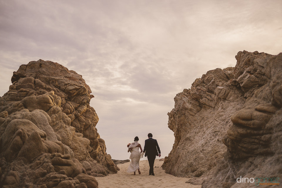 newlyweds walk on a beach path between rocks with dino gomez tak