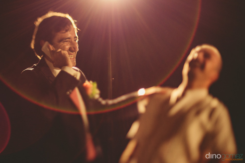 lens flare wedding photo groom makes a phone call photo by dino