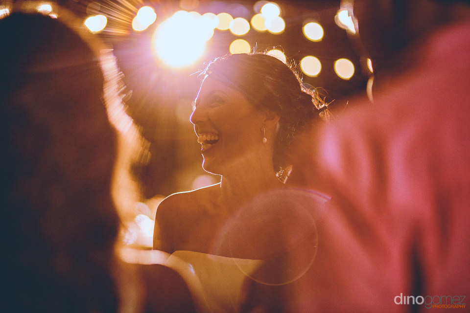 bride smiles at party after beach wedding in los cabos photos by