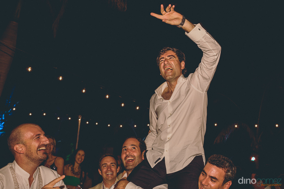 groom lifted onto the shoulders of his groomsmen in los cabos