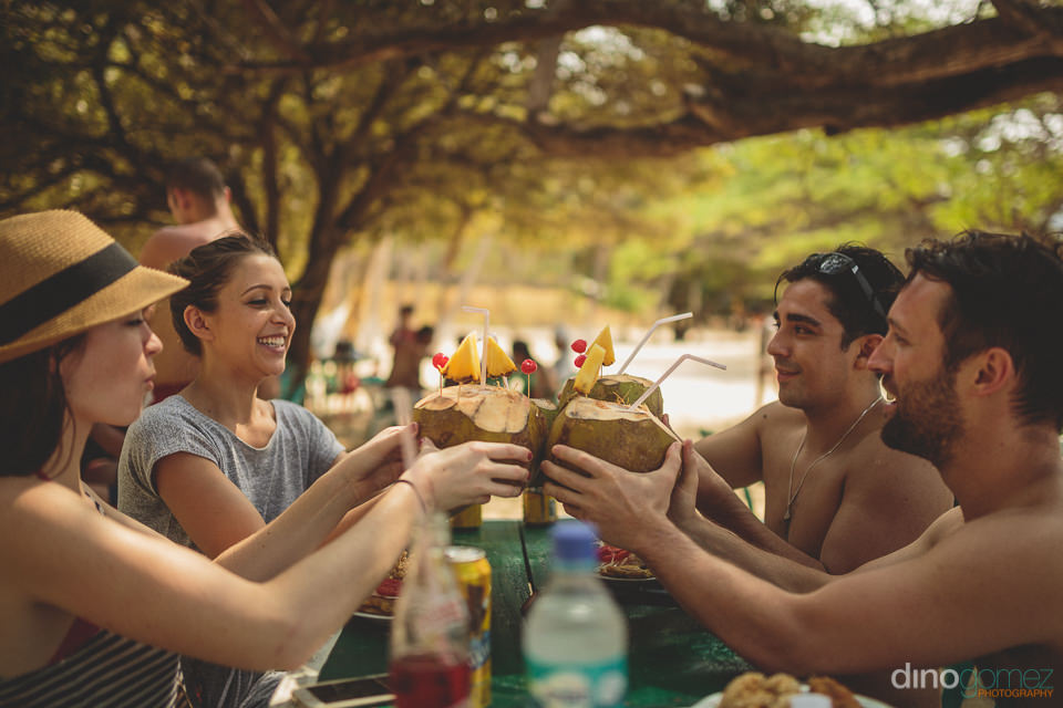 drinking from coconuts on tropical beach in colombia photo by di