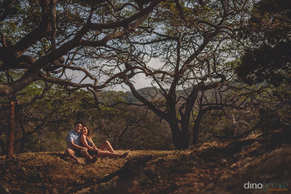 couple sitting on hill in forest in tayrona national park colomb