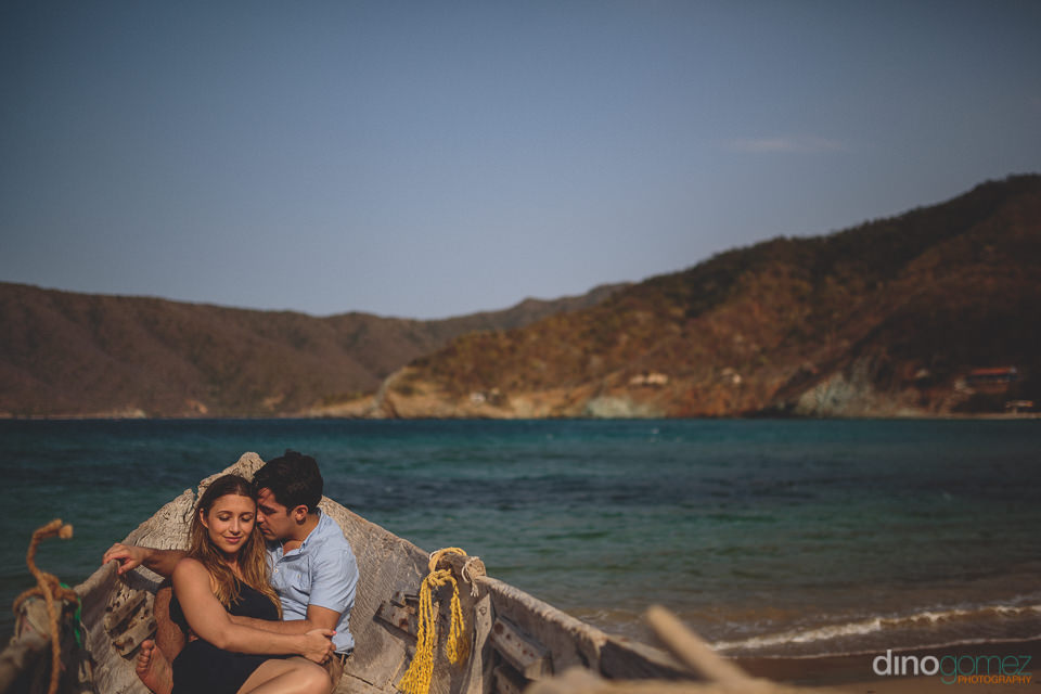 newlyweds lay in rustic boat on colombian beach