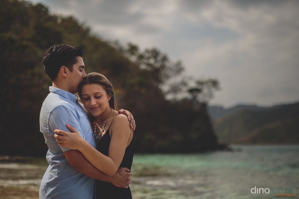 colombian newlyweds hug on the beach in parque tayrona colombia
