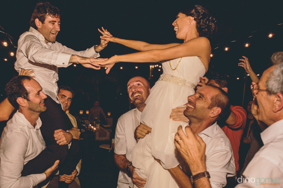 newlyweds lifted into the air by wedding guests in san jose del