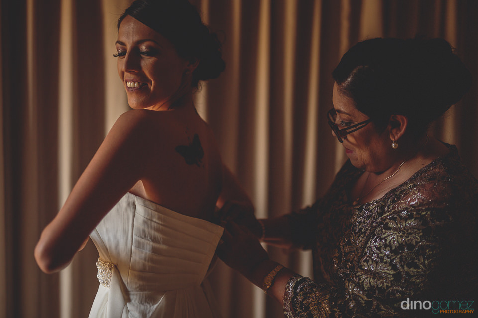 mother helps daughter into her wedding dress photo by dino gomez