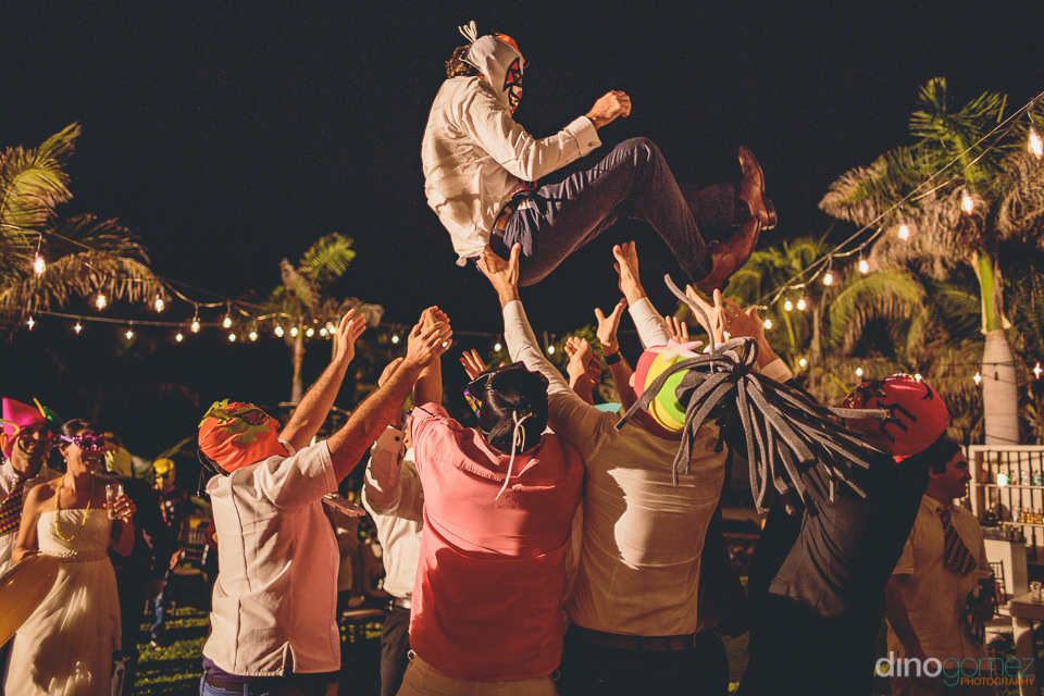 groom tossed high into the air at his los cabos wedding photogra