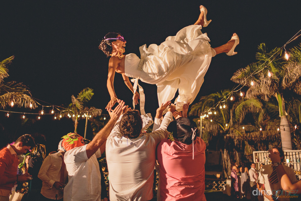 bride thrown high into the air by her wedding guests