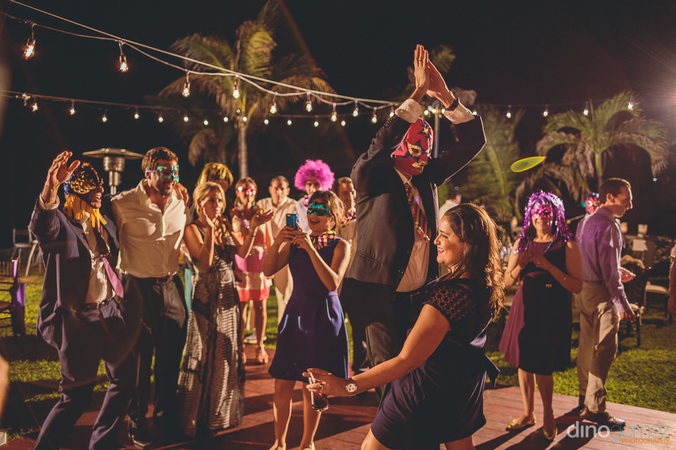 wedding guests dance while wearing costumes at claudia and jose'