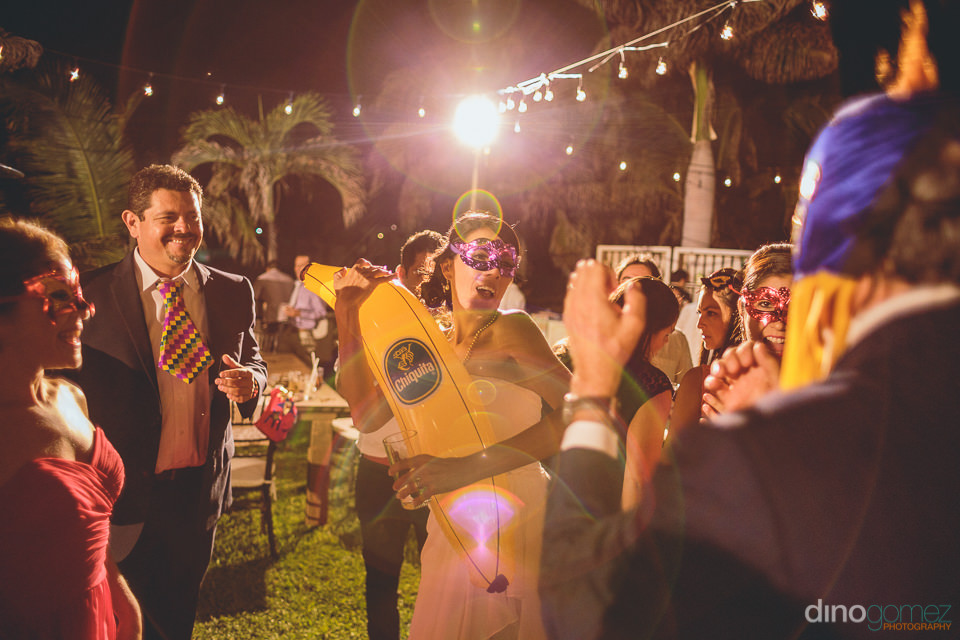 bride holds inflatable banana prop at her wedding party