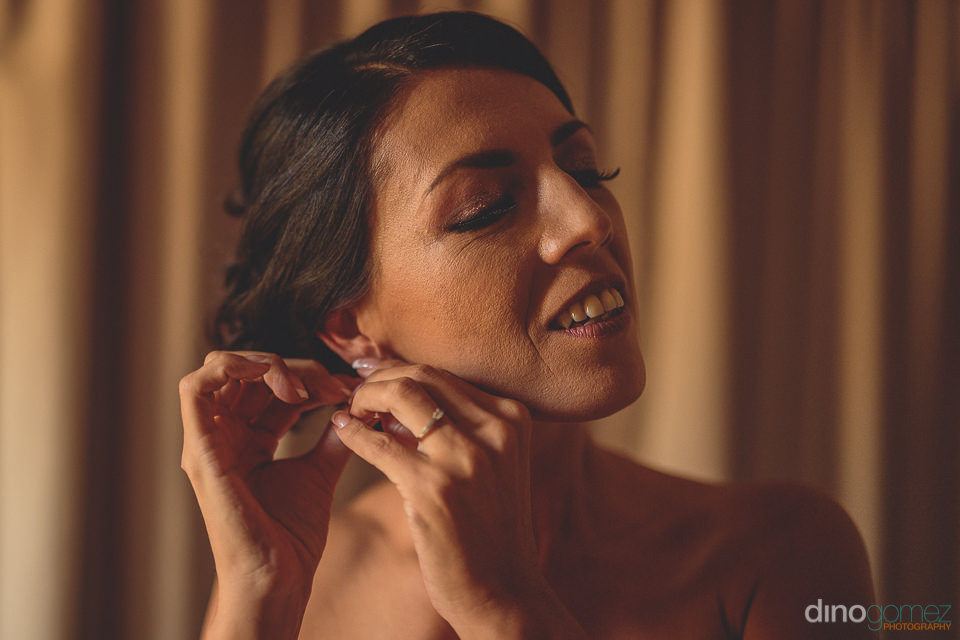 bride puts on her earrings before her wedding in mexico