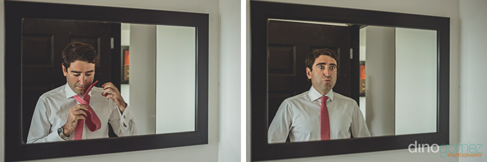 groom puts on tie and looks into mirror on wedding day