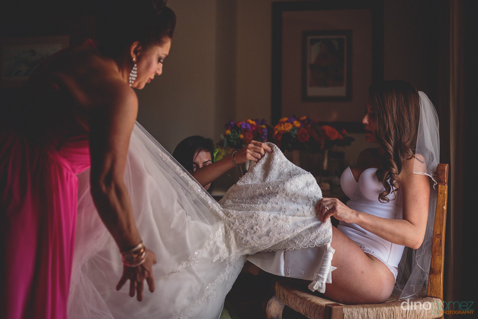 bride puts on wedding dress in puerto vallarta photo by dino gom