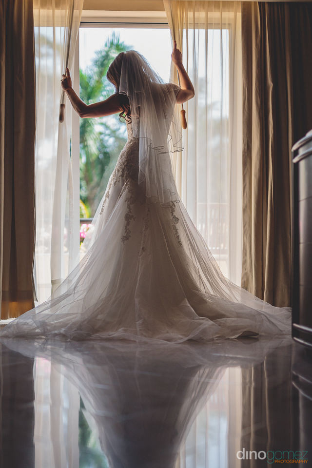 reflective photo of bride on balcony in wedding dress by dino go