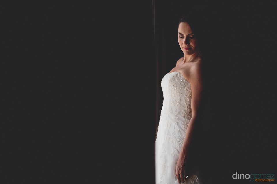 low light photo by dino gomez of bride in darkness alone
