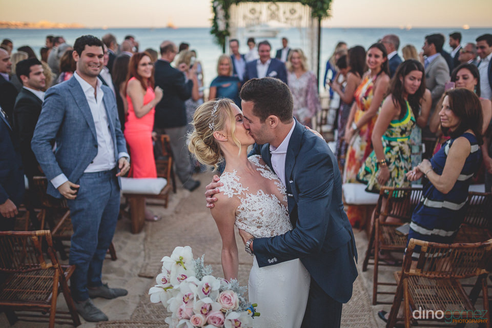 newlyweds kiss at beach wedding ceremony in cabo photo by dino g