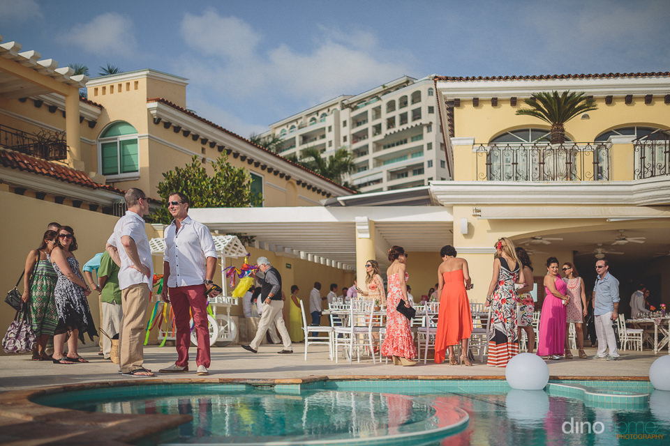 wedding guests stand by the pool at casa velas puerto vallarta d