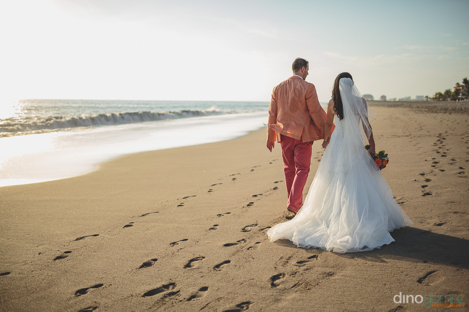 bride wearing wedding dress walks on mexico beach photo by dino