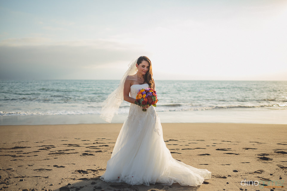bride standing in front of ocean with bouquet by cabo floral des