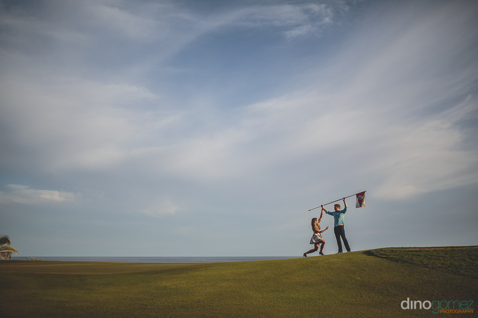 groom plants flag on sand dunes in baja mexico photo by dino gom