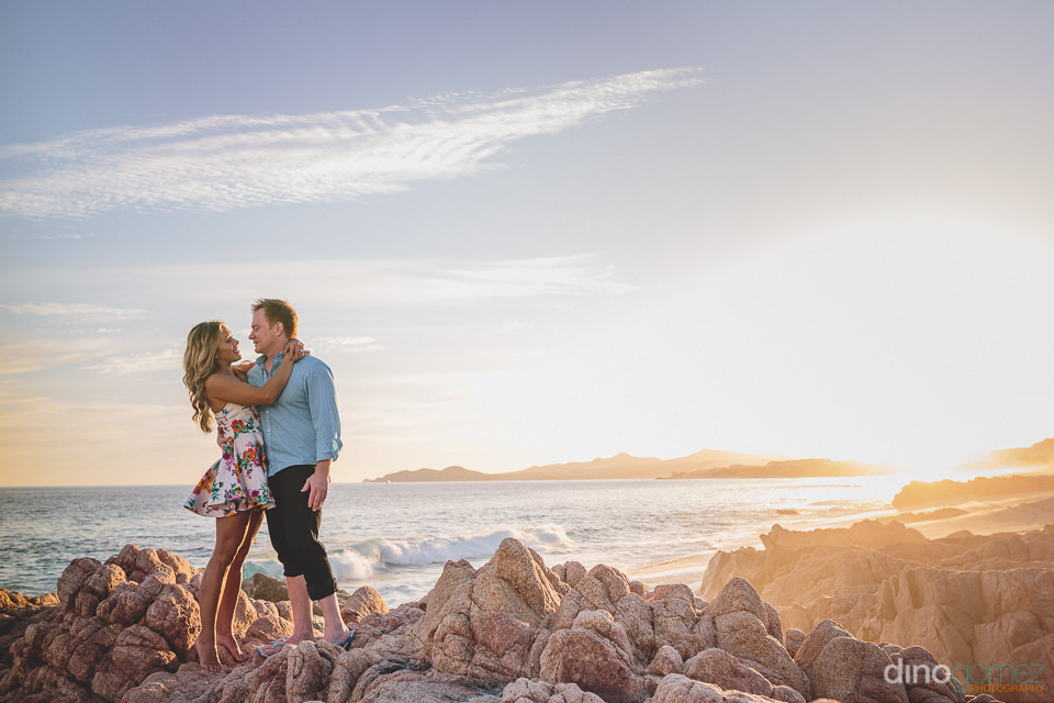 bride and groom stand on beach rocks in los cabos engagement pho