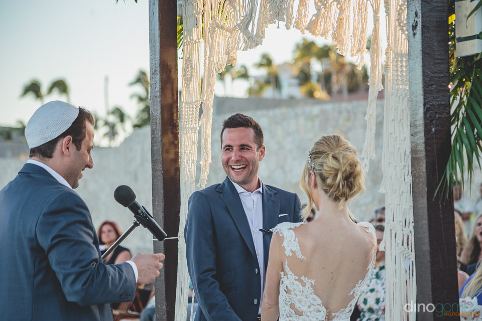 groom laughs and smiles while standing at the wedding altar in c