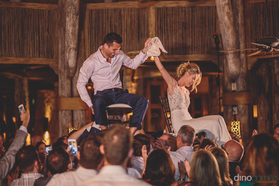 jewish tradition newlyweds lifted on chairs photo by dino gomez