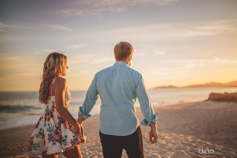 newlyweds walk hand in hand on the beach in los cabos engagement